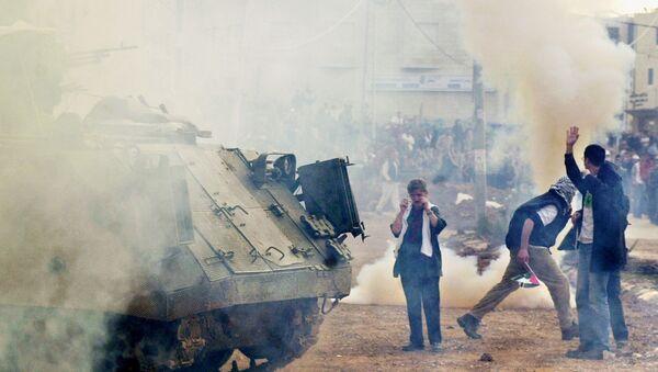 Пропалестинские демонстранты вблизи израильского бронетранспортера во время митинга в городе Рамалла на Западном берегу, 27 декабря 2001 года - Sputnik Азербайджан