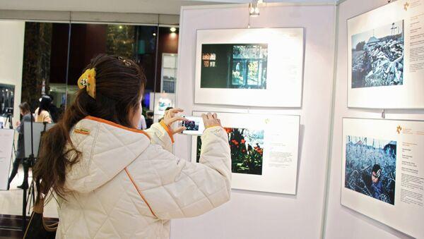 Посетительница на открытии выставки победителей конкурса имени Андрея Стенина в Пекине - Sputnik Азербайджан