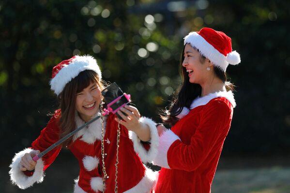 Девушки в костюмах Санта-Клаусов фотографируются во время благотворительного забега Tokyo Santa Run в Чибе - Sputnik Азербайджан