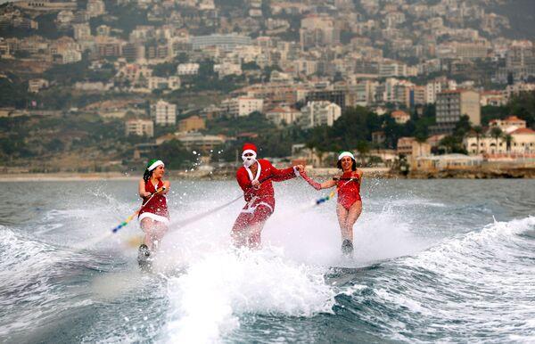 Молодые люди на водных лыжах в костюмах Санта-Клаусов в заливе Джуния, Ливан - Sputnik Азербайджан
