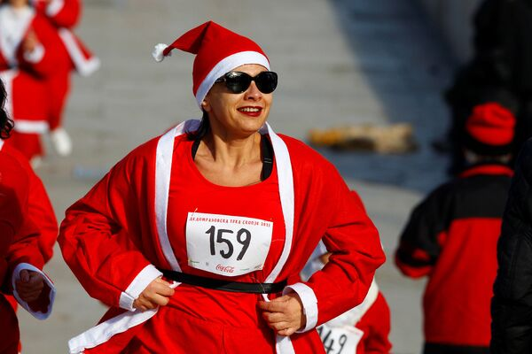 Участница ежегодного забега Санта-Клаусов в столице Македонии, Скопье - Sputnik Азербайджан