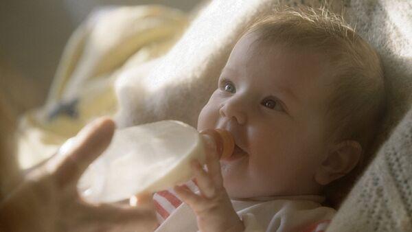 Маленькая девочка пьет из бутылочки, фото из архива - Sputnik Азербайджан
