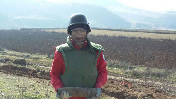Сотрудник ANAMA со снарядом, обнаруженном на территории села Алпоут Газахского района - Sputnik Азербайджан