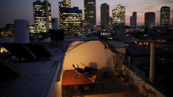 60-летний Александр Флашенберг, сидя на стуле на крыше своего дома в Тель-Авиве, наслаждается видом на море. Как говорит Александр, крыша - это его личное убежище и возможность отдохнуть от работы - Sputnik Азербайджан