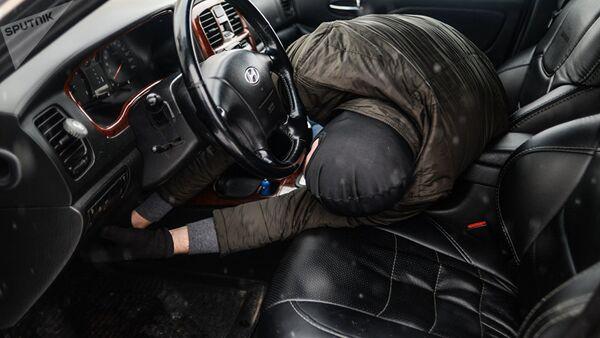 Мужчина имитирует вскрытие автомобиля и его угон, фото из архива - Sputnik Азербайджан