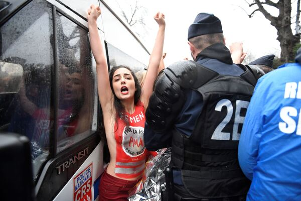 Участница движения Femen напротив сотрудника полиции на «Марше за жизнь» в Париже - Sputnik Азербайджан