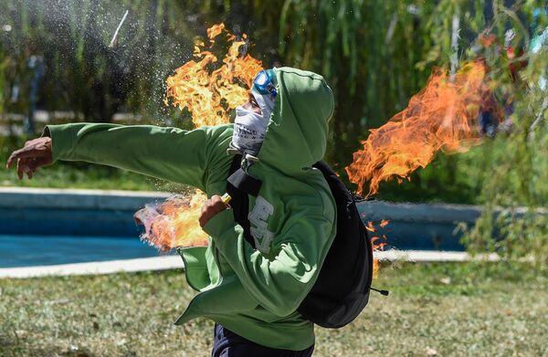 Протестующий бросает коктейль Молотова в ОМОН во время столкновений в Каракасе, связанных с ликвидацией мятежного полицейского Оскара Переса - Sputnik Азербайджан