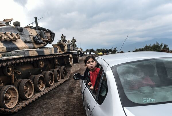 Турецкая девочка наблюдает из окна автомобиля, как танки и солдаты турецкой армии собираются у сирийской границы в городе Хасса - Sputnik Азербайджан