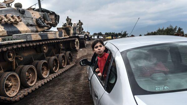 Турецкая девочка наблюдает из окна автомобиля, как танки и солдаты турецкой армии собираются у сирийской границы в городе Хасса - Sputnik Azərbaycan
