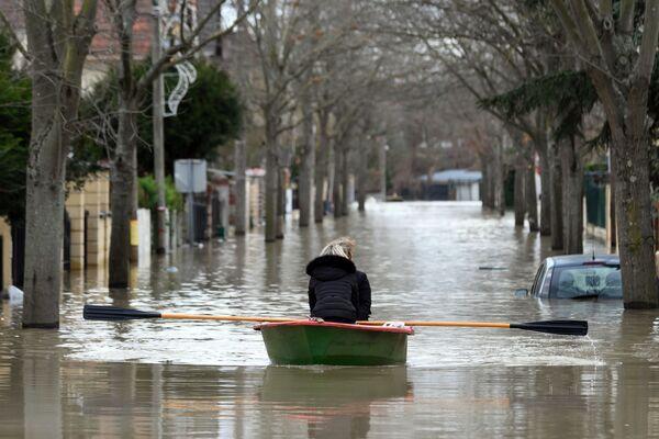 Местные жители переправляются на лодке на одной из затопленной улице в Париже - Sputnik Азербайджан