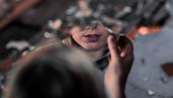 Девушка рассматривает свое отражение на куске зеркала, фото из архива - Sputnik Азербайджан