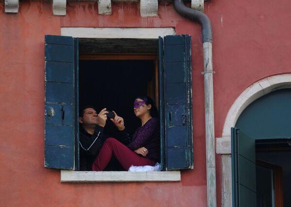 Мужчина в окне фотографирует праздничное парад гондол на Гранд-канале во время Венецианского карнавала - Sputnik Азербайджан