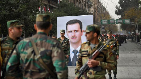 Сирийские солдаты проходят мимо портрета президента Башара аль-Асада во время правительственного праздника, посвященного первой годовщине возвращения северного сирийского города Алеппо, недалеко от площади Саадаллы аль-Джабири 21 декабря 2017 года - Sputnik Азербайджан