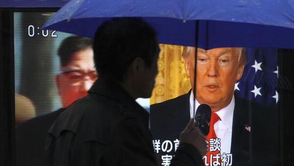 Мужчина проходит перед экраном телевизора с изображением северокорейского лидера Ким Чен Ына и президента США Дональда Трампа, фото из архива - Sputnik Азербайджан