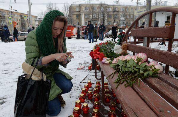 Женщина зажигает свечу возле здания торгового центра «Зимняя вишня» в Кемерово, где произошел пожар - Sputnik Азербайджан