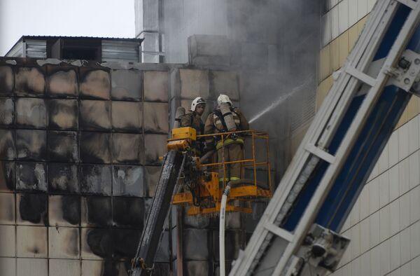 Сотрудники пожарной охраны МЧС во время тушения пожара в торговом центре «Зимняя вишня» в Кемерово - Sputnik Азербайджан