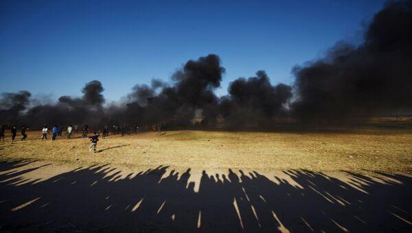 Палестинские протестующие во время столкновений с израильскими военными на границе сектора Газа и Израиля - Sputnik Azərbaycan
