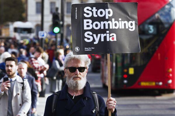 Мужчина держит плакат, призывающей не бомбить Сирию, на акции протеста против ударов по Сирии в Лондоне - Sputnik Азербайджан