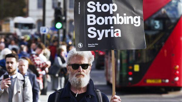 Мужчина держит плакат, призывающей не бомбить Сирию, на акции протеста против ударов по Сирии в Лондоне - Sputnik Azərbaycan