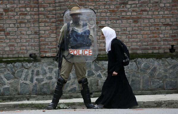 Мусульманская студентка идет мимо индийского полицейского во время протеста против недавних случаев изнасилования в городе Сринагар в Кашмире, Индия - Sputnik Азербайджан
