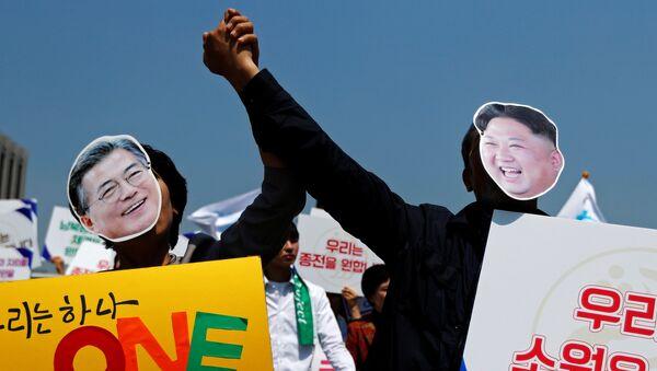 Cənubi Koreya prezidenti Moon Jae və Şimali Koreyanın lideri Kim Jong Unun maskalarını taxmış insanlar - Sputnik Azərbaycan