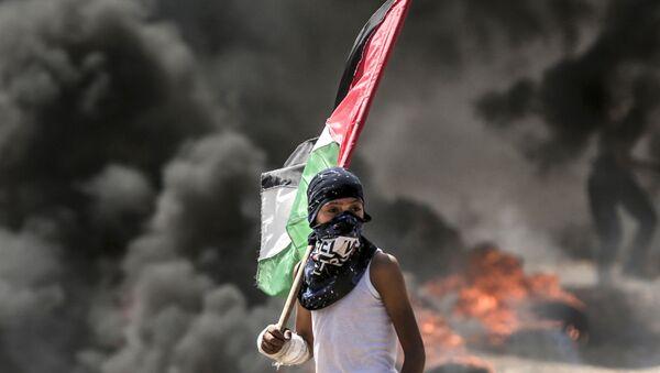 Палестинский демонстрант во время столкновений с израильскими силами у границы между сектором Газа и Израилем - Sputnik Азербайджан