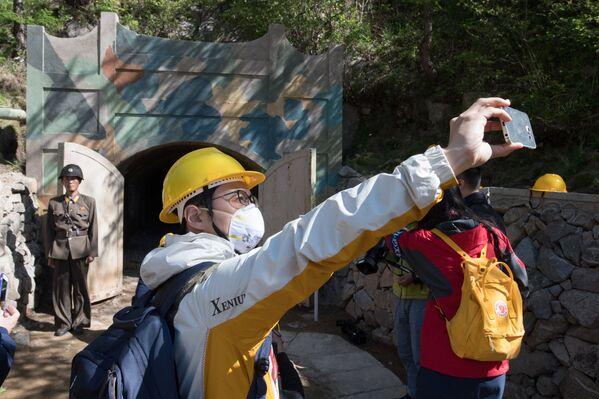 Журналисты из южной Кореи фотографируются у входа в одну из шахт во время закрытия ядерного полигона Пхунгери на севере КНДР - Sputnik Азербайджан