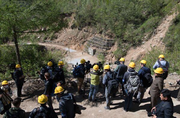 Иностранные журналисты неподалеку от шахты для ядерных испытаний №4 на ядерном полигоне Пхунгери на севере КНДР - Sputnik Азербайджан