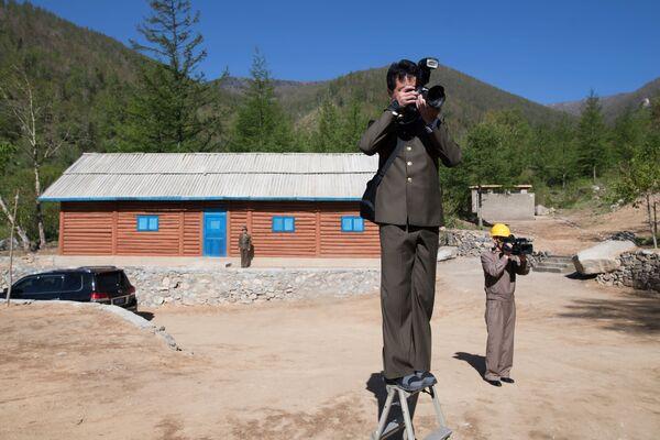 Журналисты из КНДР у здания управления шахтой для ядерных испытаний №2 на ядерном полигоне Пхунгери на севере КНДР - Sputnik Азербайджан