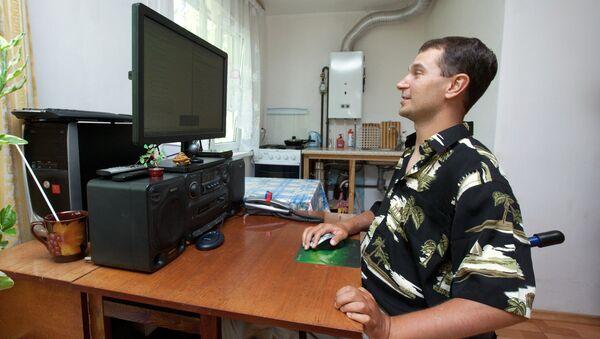 Мужчина с ограниченными физическими возможностями занимается удаленной работой у себя дома, фото из архива - Sputnik Азербайджан