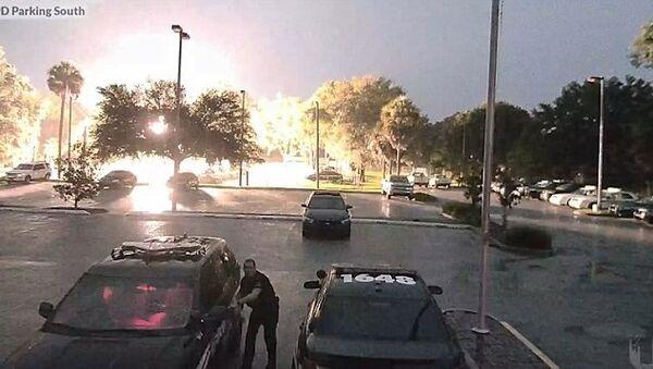 Полицейский бежит к своей машине во время удара молнии - Sputnik Азербайджан