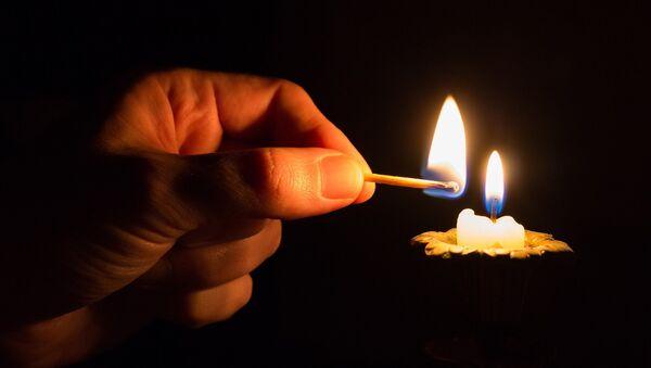 Человек зажигает свечу в темноте, фото из архива - Sputnik Azərbaycan
