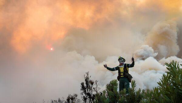 Пожарный сигнализирует членам расчета об опасности, архивное фото - Sputnik Азербайджан