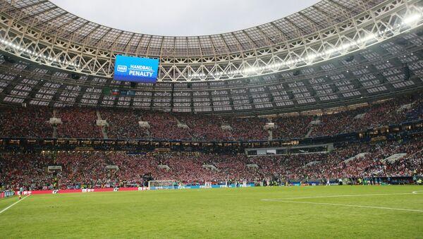 На дальнем плане на экране: решение о пенальти из-за игры рукой в финальном матче чемпионата мира по футболу между сборными Хорватии и Франции - Sputnik Азербайджан