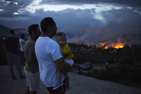 Мужчина с ребенком на руках смотрит на с холма на пожары в окрестностях Афин - Sputnik Азербайджан
