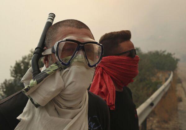 Люди закрывают лица, защищаясь от дыма лесных пожаров, бушующих в окрестностях Афин - Sputnik Азербайджан