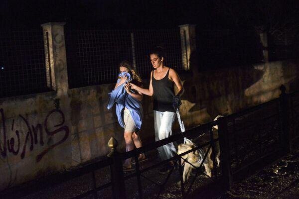 Две девушки эвакуируются из-за бущующих лесных пожаров из населенного пункта, расположенного в окрестностях Афин - Sputnik Азербайджан