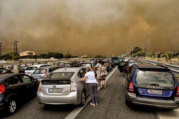 Люди рядом со своими автомобилями на закрытой дороге рядом с зоной лесных пожаров в греческой деревне Кинета - Sputnik Азербайджан