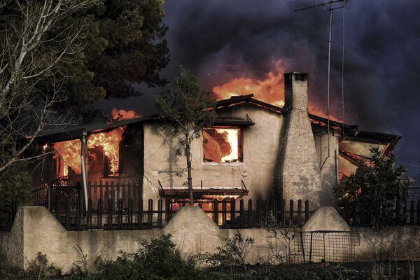 Горящий дом, попавший в зону лесных пожаров в окрестностях Афин, Греция - Sputnik Азербайджан