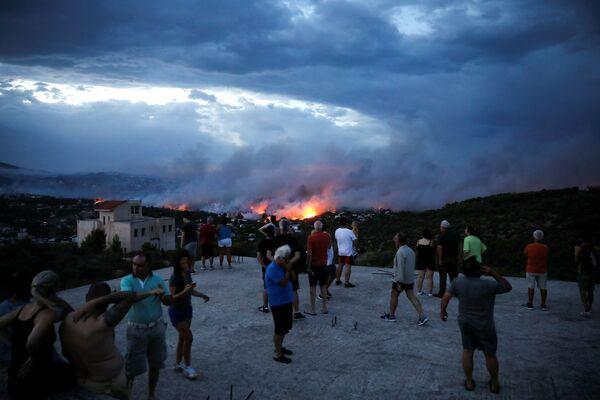 Люди наблюдают на распространением лесного пожара в греческом городе Рафина рядом с Афинами - Sputnik Азербайджан