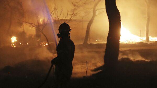 Пожарный в зоне лесного пожара к востоку от Афин - Sputnik Азербайджан