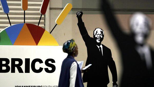 Журналист проходит мимо плаката Нельсона Манделы во время саммита БРИКС в Йоханнесбурге, Южная Африка - Sputnik Азербайджан