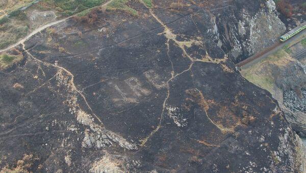 Надпись, вкопанная в землю и образующая слово Éire — Ирландия — на холме Брей-Хед в графстве Уиклоу - Sputnik Азербайджан