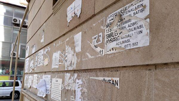 Заклеенная объявлениями стена жилого дома в Баку - Sputnik Azərbaycan