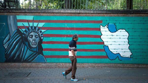 Мужчина проходит перед антиамериканской росписью на стене на одной из улиц Тегерана, фото из архива - Sputnik Азербайджан