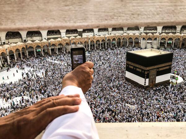 Паломник снимает на телефон молитвенное движение вокруг Каабы в Заповедной мечети Мекки - Sputnik Азербайджан