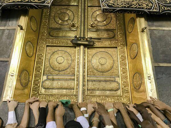 Мусульманские паломники у золотой двери Каабы в мечети аль-Харам перед хаджем, Мекка - Sputnik Азербайджан
