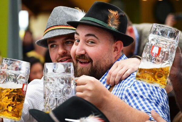 Посетители с бокалами пива на открытии традиционного пивного фестиваля Октоберфест в Мюнхене - Sputnik Азербайджан