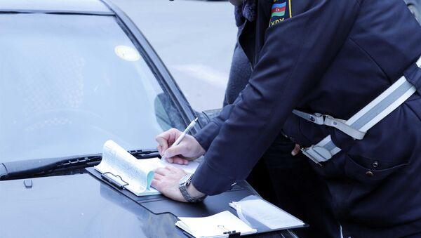 Сотрудник дорожной полиции составляет протокол об административном правонарушении, фото из архива - Sputnik Азербайджан
