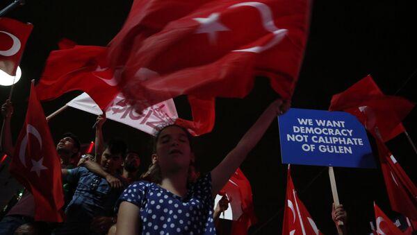 Сторонники президента Турции Реджепа Тайипа Эрдогана держат плакаты и размахивают национальными флагами во время проправительственного митинга на главной площади в Анкаре, фото из архива - Sputnik Азербайджан